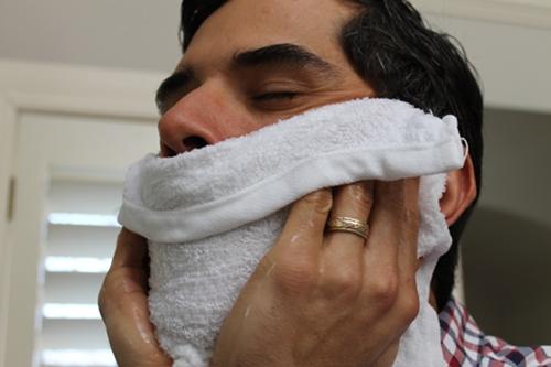 homem passando toalha quente no rosto para abrir os poros